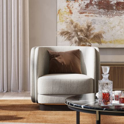 A luxurious velvet armchair with a wooden base and gold detailing. Pictured in Xangai Beige.