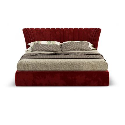A classic velvet upholstered bed with a fluted and fan-shaped headboard.