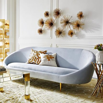 A contemporary sofa with a curved back and brass legs