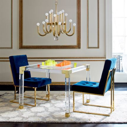 A contemporary brass and acrylic games tale with a glass surface