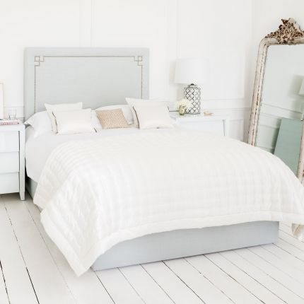 Luxury blue grey linen bed with an elegant tall headboard, with an art deco studding design